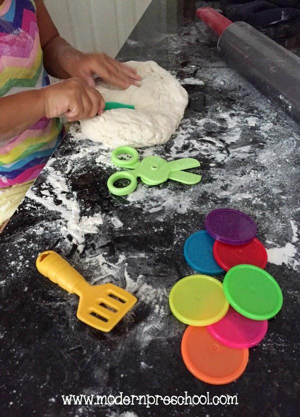 Pizza dough pretend play! Give preschoolers dough to strengthen fine motor skills through play from Modern Preschool.