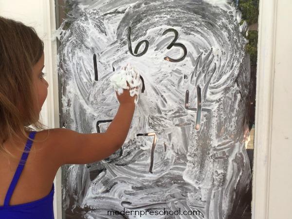 Shaving cream writing on windows! Move the learning outside! {Modern Preschool}