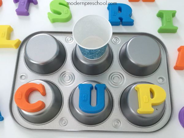 Spelling CVC words with letter magnets on muffin tins from Modern Preschool
