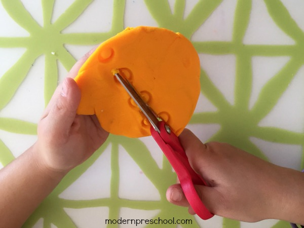 Practice toddler and preschool scissor skills with play dough! A fun, simple way to encourage proper scissor grip and use while cutting with fine motor skills.