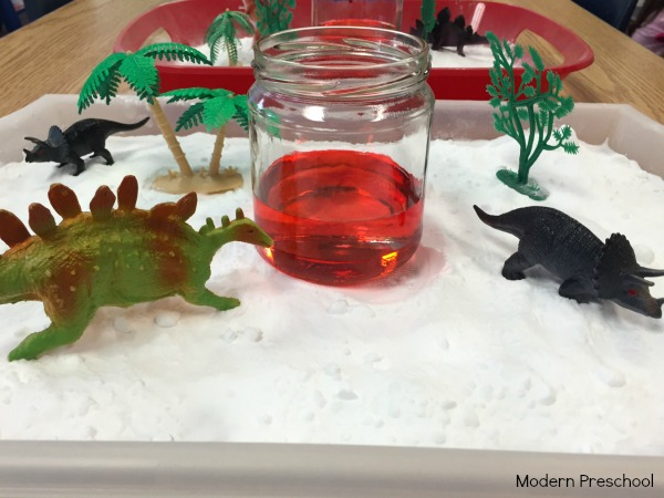 Kids can discover and explore chemical reactions made with baking soda and vinegar in this simple dinosaur and lava themed activity tray!
